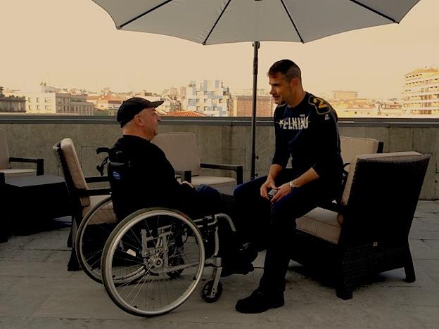 una personas con discapacidad y otra sin ella hablando en la terraza del hotel