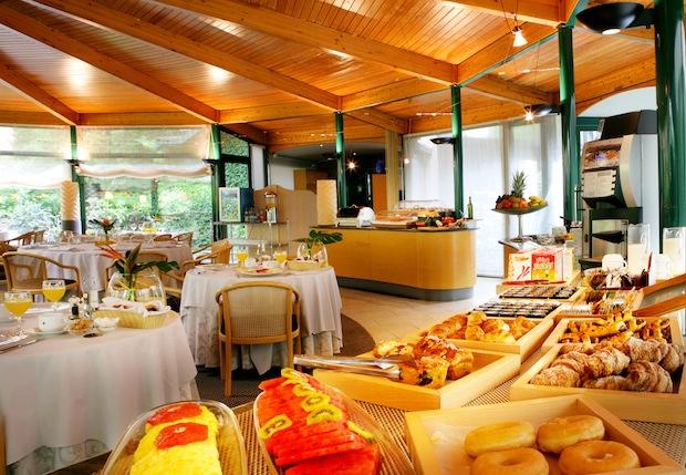 bufet libre con mesas al fondo y un primer plano con platos de desayuno