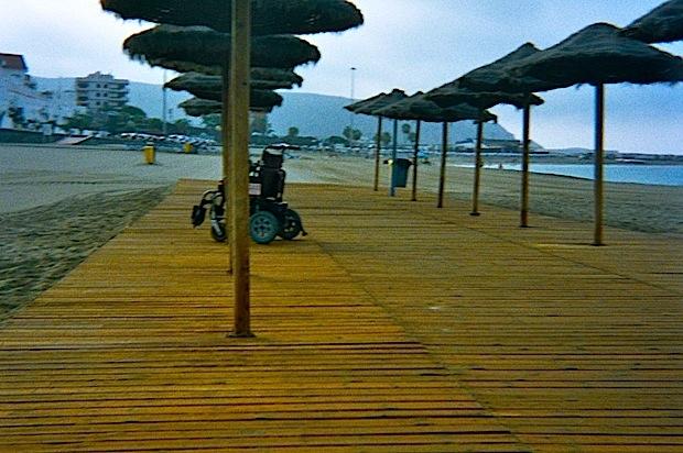silla eléctrica sobre plataforma de madera y sombrillas