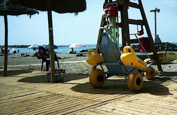 silla anfíbia sobre plataforma de madera y sombrillas junto al mar