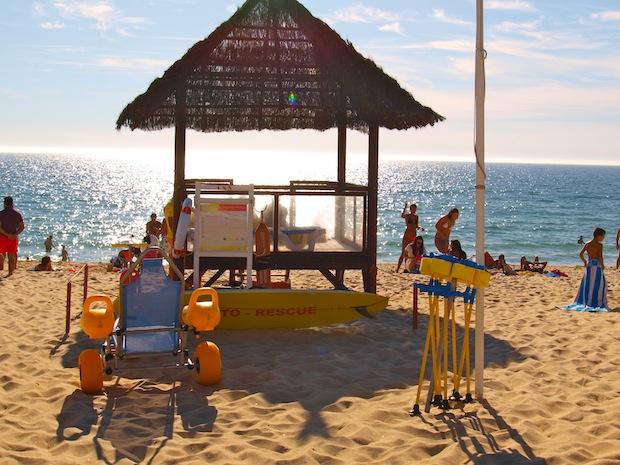 puesto de guardacostas con silla y bastones anfíbios sobre arena de playa