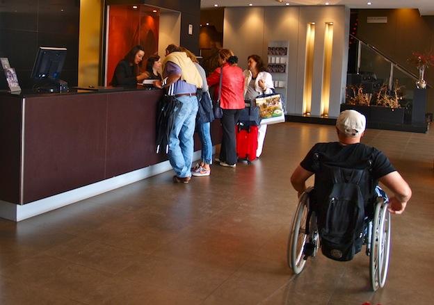 viajero con silla de ruedas en la recepción de un hotel