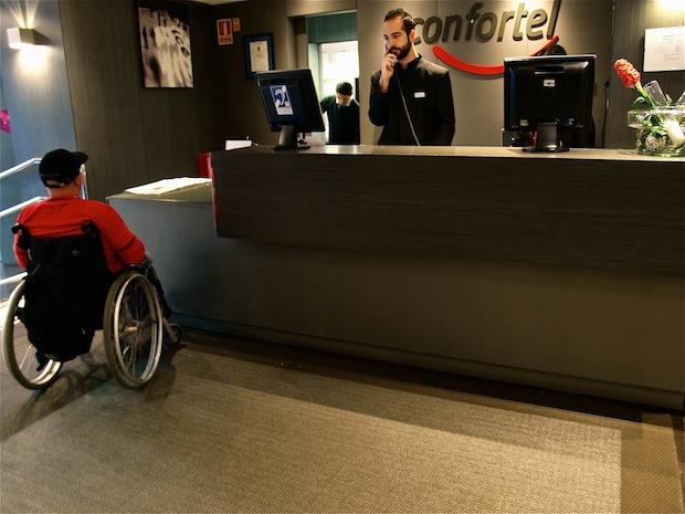 un viajero con silla de ruedas en el mostrador adaptado