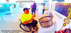 Miguel tocando el tambor en el museo con su silla de ruedas